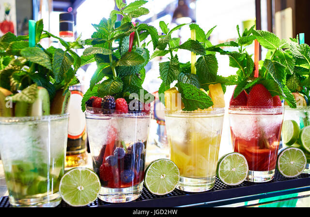 Fruit and berry cocktails with mint on the counter of a cafe - Stock Image