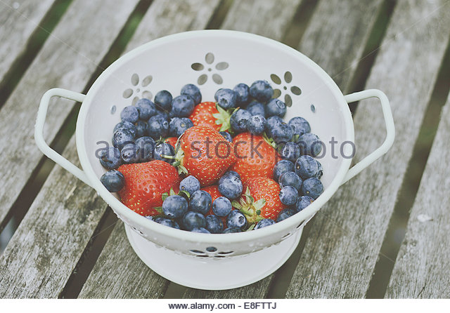 Colander with strawberries and blueberries - Stock Image