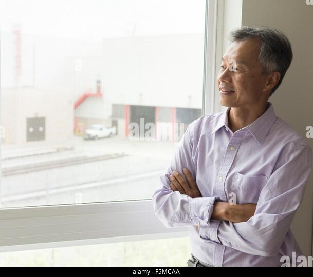 Waist up of mature man looking out of window arms crossed - Stock Image