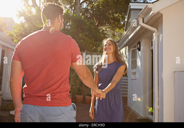 Happy young woman holding hand of her boyfriend and walking around their house. Loving young couple outdoors in - Stock-Bilder