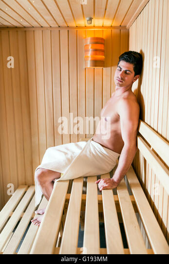 Handsome man relaxing in a sauna with towel wrapped around his waist - Stock Image