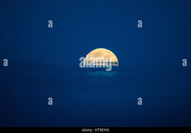 Aberystwyth Wales UK, Monday 13 March 2017 UK Weather: The full moon setting at daybreak in Aberystwyth on the west - Stock Image