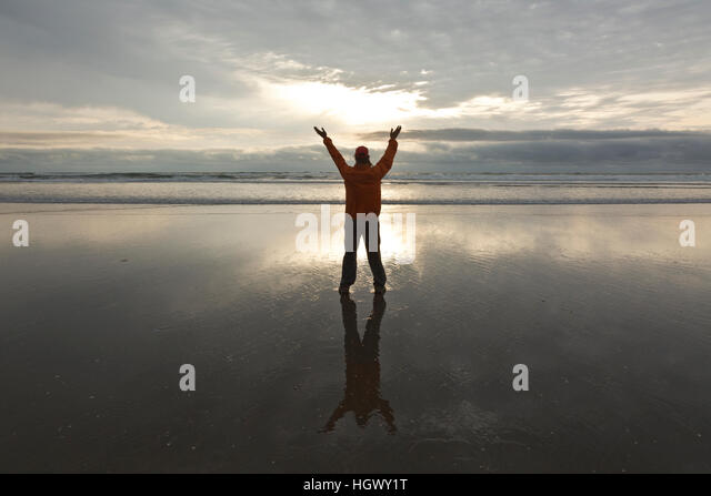 OR02325-00...OREGON - Person expressing feeling on Canon Beach at sunset. - Stock Image