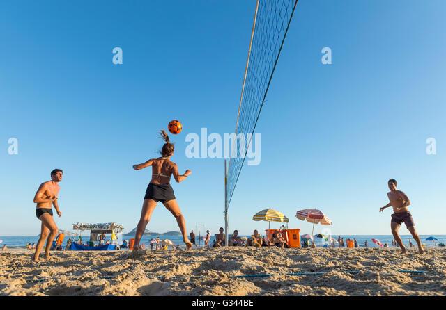 RIO DE JANEIRO - MARCH 17, 2016: Young Brazilian men and women play futevolei (footvolley), combining football and - Stock Image