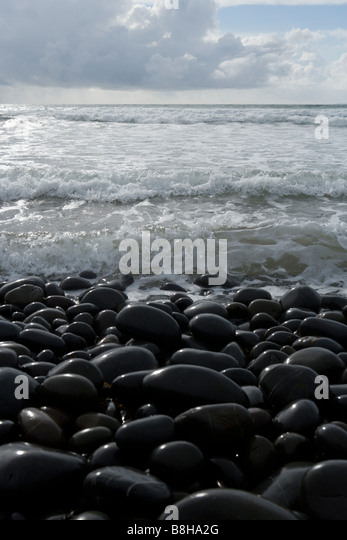 Pebbles and shallow water - Stock Image