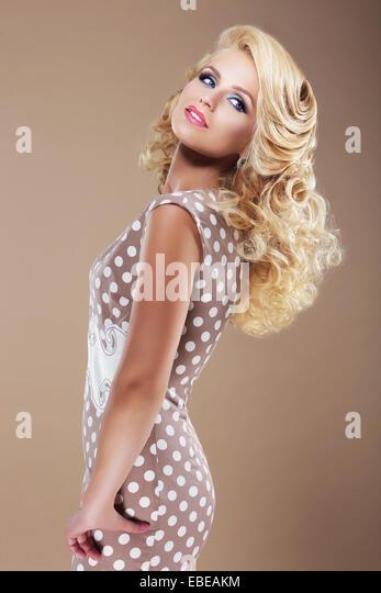 Graceful Woman in Retro Polka Dot Dress Looking Back - Stock Image