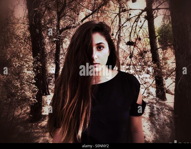 Young teenage girl hair covering face in the forest - Stock Image