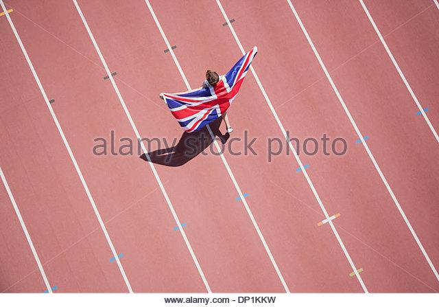 Runner celebrating with British flag on track - Stock Image