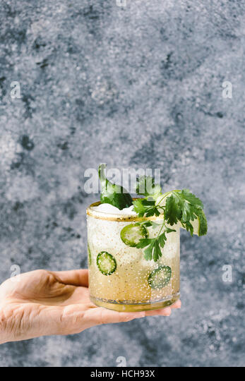 A glass of spicy jalapeno margarita is photographed in a woman's hand from the front view. - Stock Image