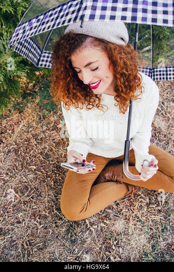 Young redhead woman so happy using her mobile phone - Stock Image