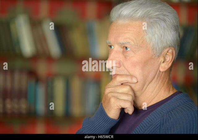 Elderly  man near bookshelves - Stock Image