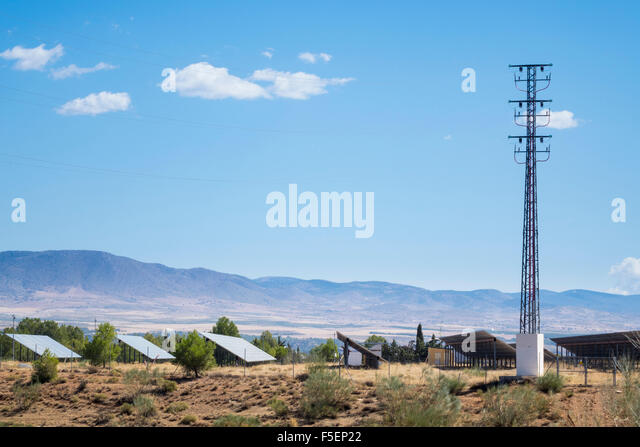 Row of solar panels and electricity pylon in Southern Spain - Stock Image