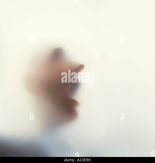 Man with face against frosted glass - Stock-Bilder