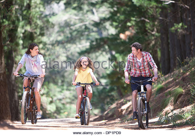 Family riding bicycles in woods - Stock Image