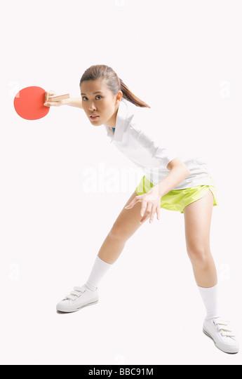 Young woman playing table tennis, studio shot - Stock Image