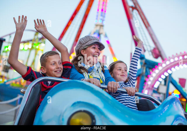 Mature woman with son and daughter on fairground ride - Stock Image