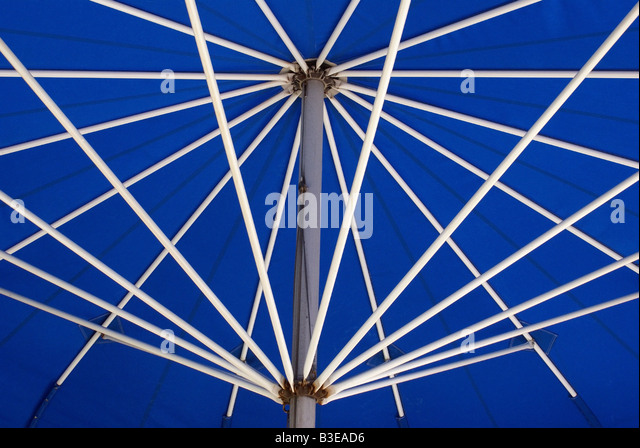 Supporting poles hold up an open umbrella - Stock Image
