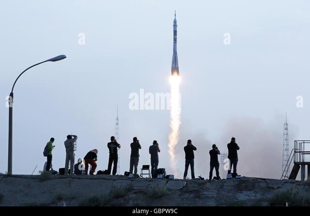 Baikonur Cosmodrome, Kazakhstan. 7th July, 2016. Photographers watch a Soyuz-FG rocket booster carrying the Soyuz - Stock Image