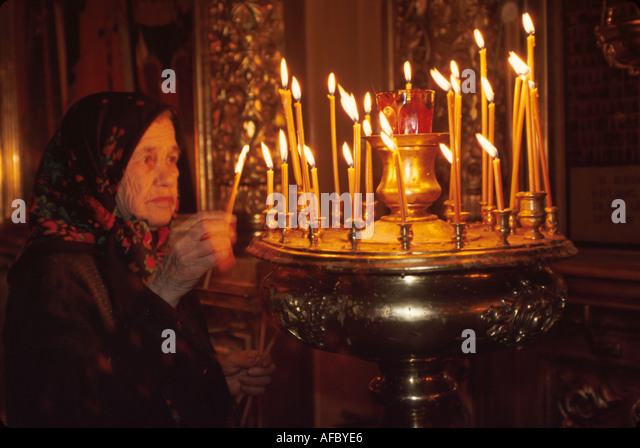 Russia former Soviet Union Moscow Orthodox church interior senior woman lights memorial candles - Stock Image
