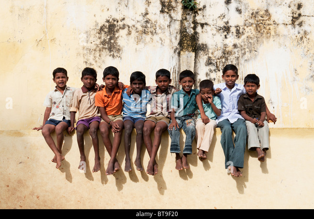 Rural South Indian village boys sitting on school wall in bright sunlight. - Stock Image
