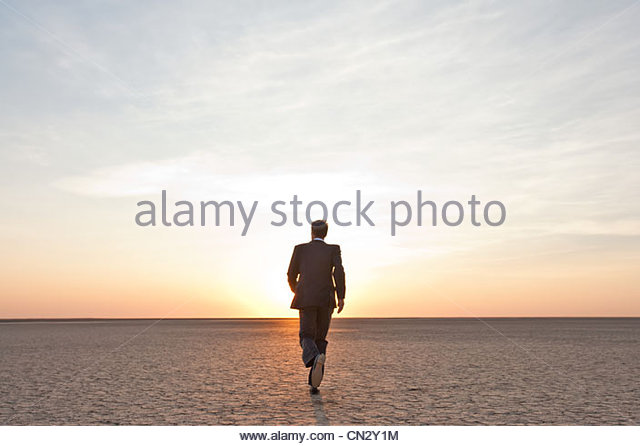 Businessman walking alone in the desert - Stock Image