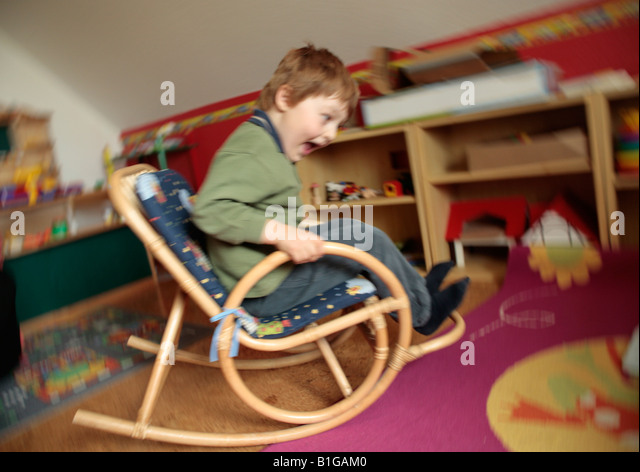 young boy rocking on a rocking chair - Stock Image