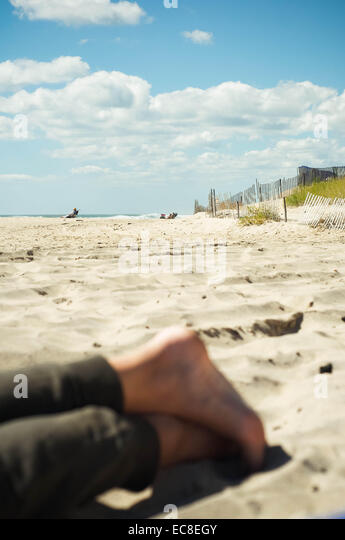 A young Canadian holidaying in New York soaks up the sun on a Montauk beach on the last official day of Summer in - Stock Image