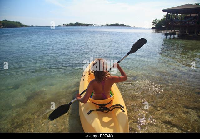 Roatan, Bay Islands, Honduras; A Young Woman Paddling A Kayak At Anthony's Key Resort - Stock Image