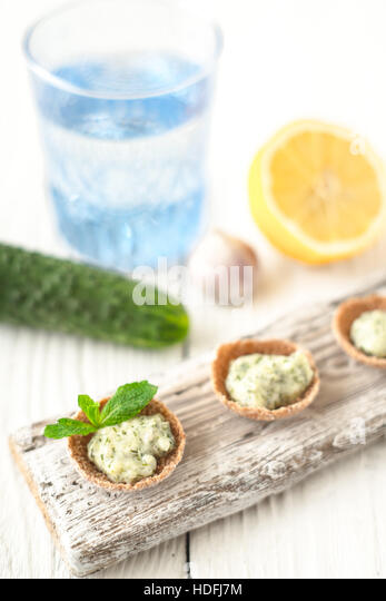Crisp bread with tzatziki on the white wooden board vertical - Stock Image