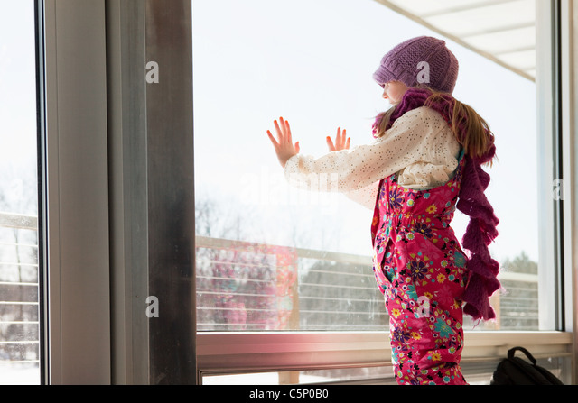 Girl looking through window - Stock-Bilder