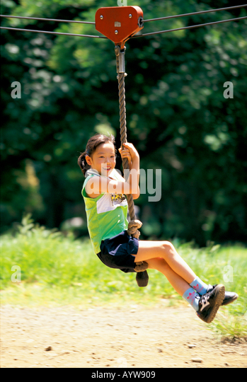 Girl playing with play equipment in the park - Stock-Bilder
