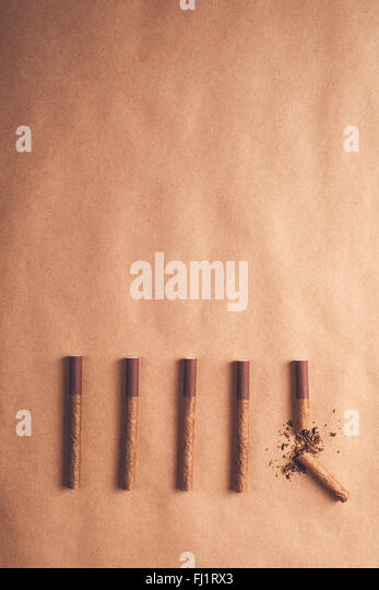 Quit smoking concept, flat lay arranged cigarettes with broken one at the end as final decision to quit is made - Stock-Bilder