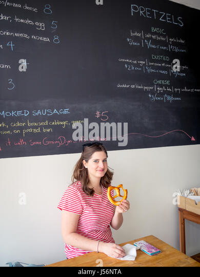 A pretty brunette girl holds up a salt-and-butter soft pretzel from Zwick's Pretzels in Edmonton, Alberta, Canada. - Stock Image