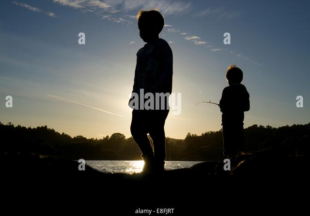 Norway, Tromay, Kids (2-3, 8-9) fishing at sunset - Stock Image