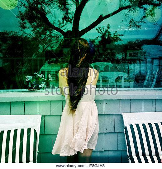 Girl looking through window - Stock Image