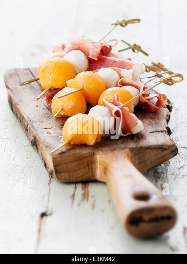 Mozzarella, prosciutto, melon canapes on textured background - Stock Image