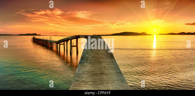 Sunrise over the sea. Pier on the foreground. Panorama - Stock Image