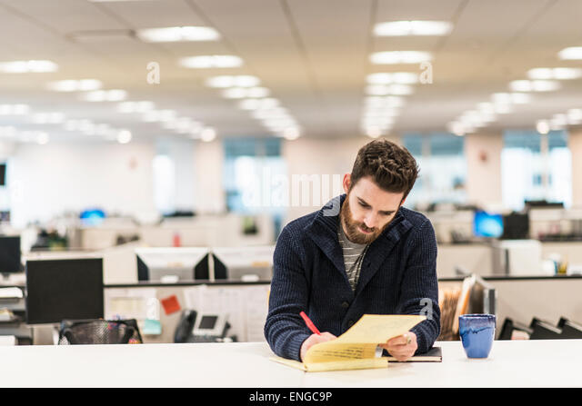 A man sitting at a desk in an office writing with a red pen. - Stock Image