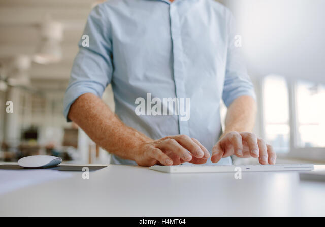 Close up of businessman hands typing on computer keyboard. Cropped shot young man working on computer while standing - Stock Image
