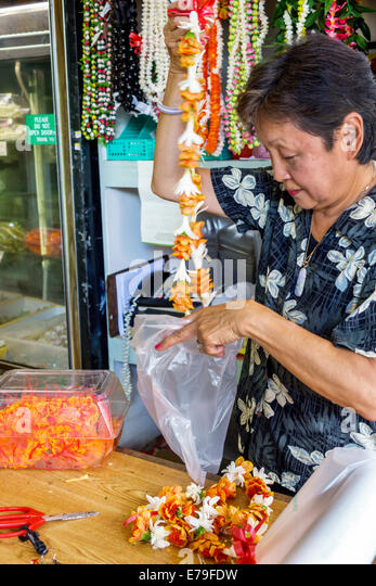 Hawaii Hawaiian Oahu Honolulu Chinatown Kekaulike Street florist shop flower leis sale Asian woman manager owner - Stock Image