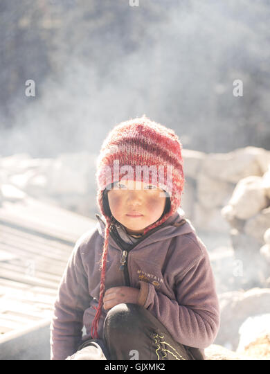 A young Nepalese girl sits in the cold winter near Namche - Stock Image
