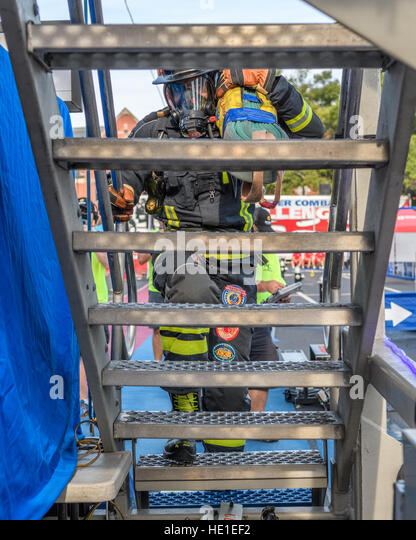 A firefighter starts up stairs on a four story tower carrying bundled hose. - Stock Image