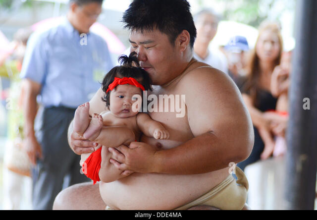 Wrestlers and babies take part in a sumo event at Matsuo Taisha Shrine in Kyoto, Japan. - Stock-Bilder