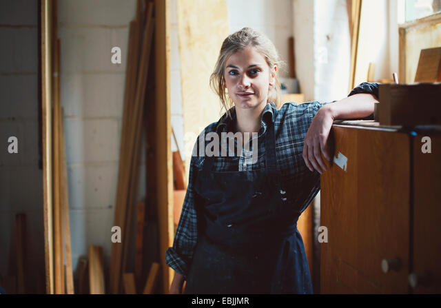 Portrait of young craftswoman leaning on cupboard in organ workshop - Stock Image