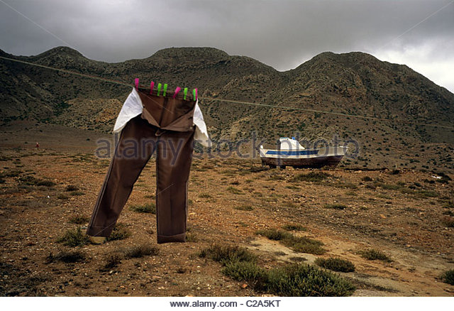 Trousers hang on a line near a beached boat. - Stock Image