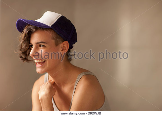 Young woman wearing cap, smiling - Stock Image
