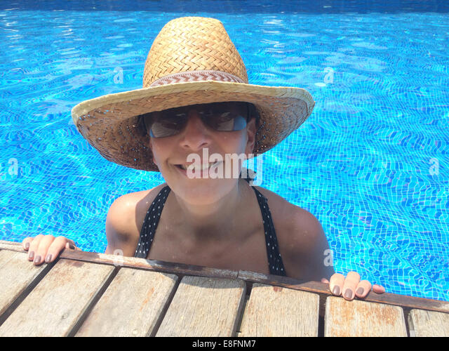 Smiling woman in swimming pool, wearing straw hat - Stock Image