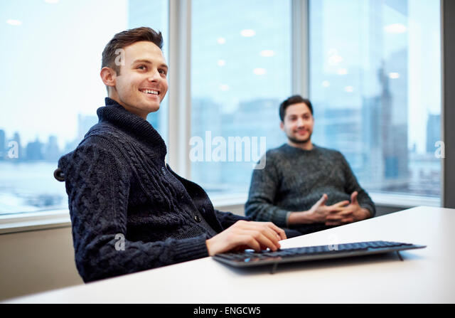 Two men in a office seated at a desk chatting and smiling. - Stock Image