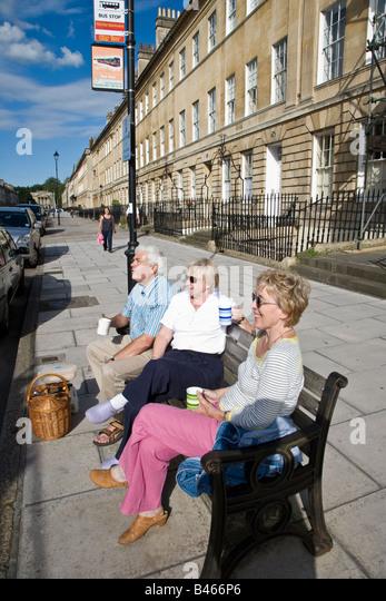 People having a tea picnic on bench in street Bath UK - Stock Image