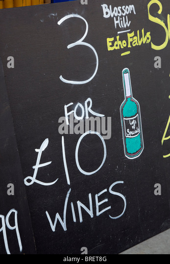 Boards advertising cheap wines outside an off license shop. UK, Britain - Stock Image